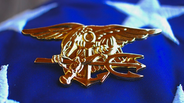 Navy SEAL trident rests atop a folded American flag. (iStock)