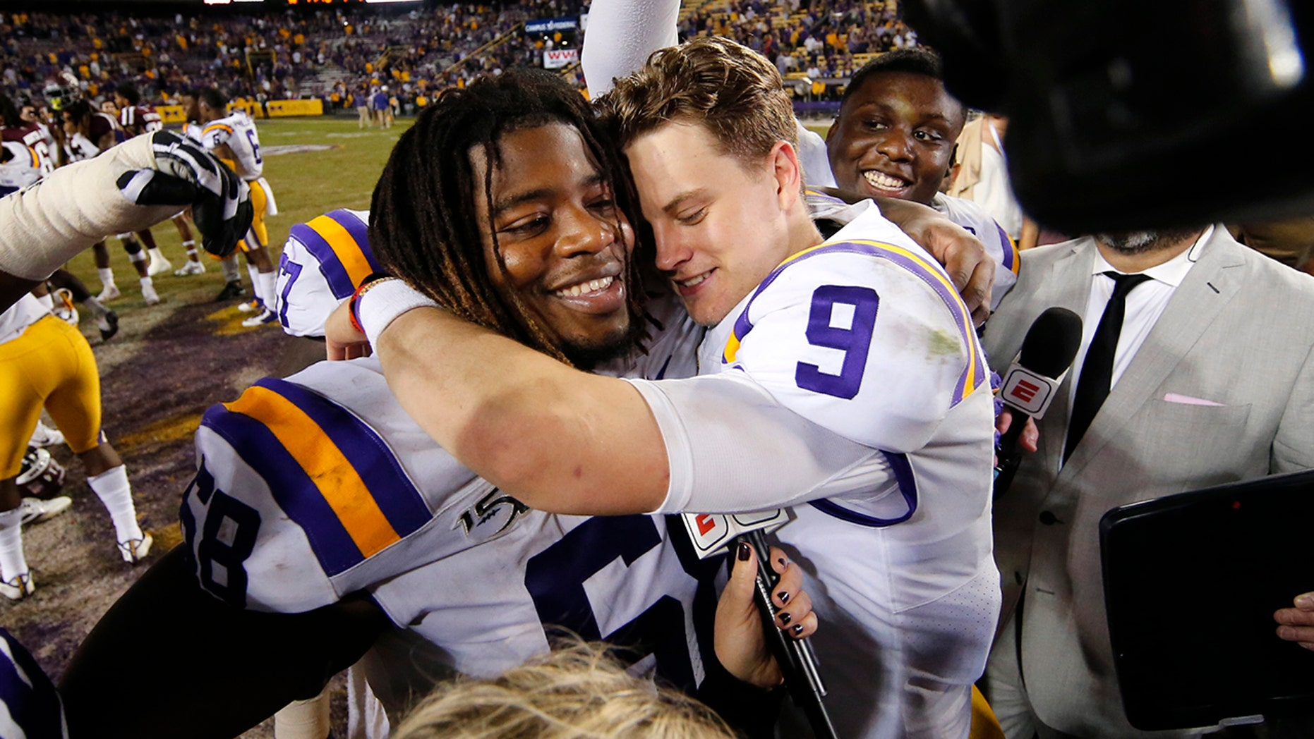 LSU quarterback Joe Burrow (9) hugs ensure Damien Lewis after a team's NCAA college football diversion opposite Texas Aamp;M in Baton Rouge, La., Saturday, Nov. 30, 2019. LSU won 50-7. (AP Photo/Gerald Herbert)