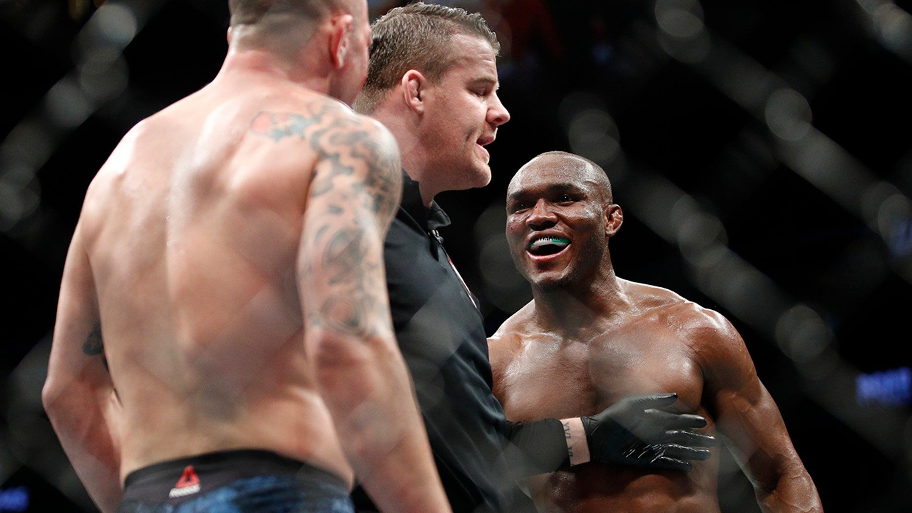Kamaru Usman, right, taunts Colby Covington in a mixed martial arts welterweight championship bout at UFC 245, Saturday, Dec. 14, 2019, in Las Vegas. (AP Photo/John Locher)