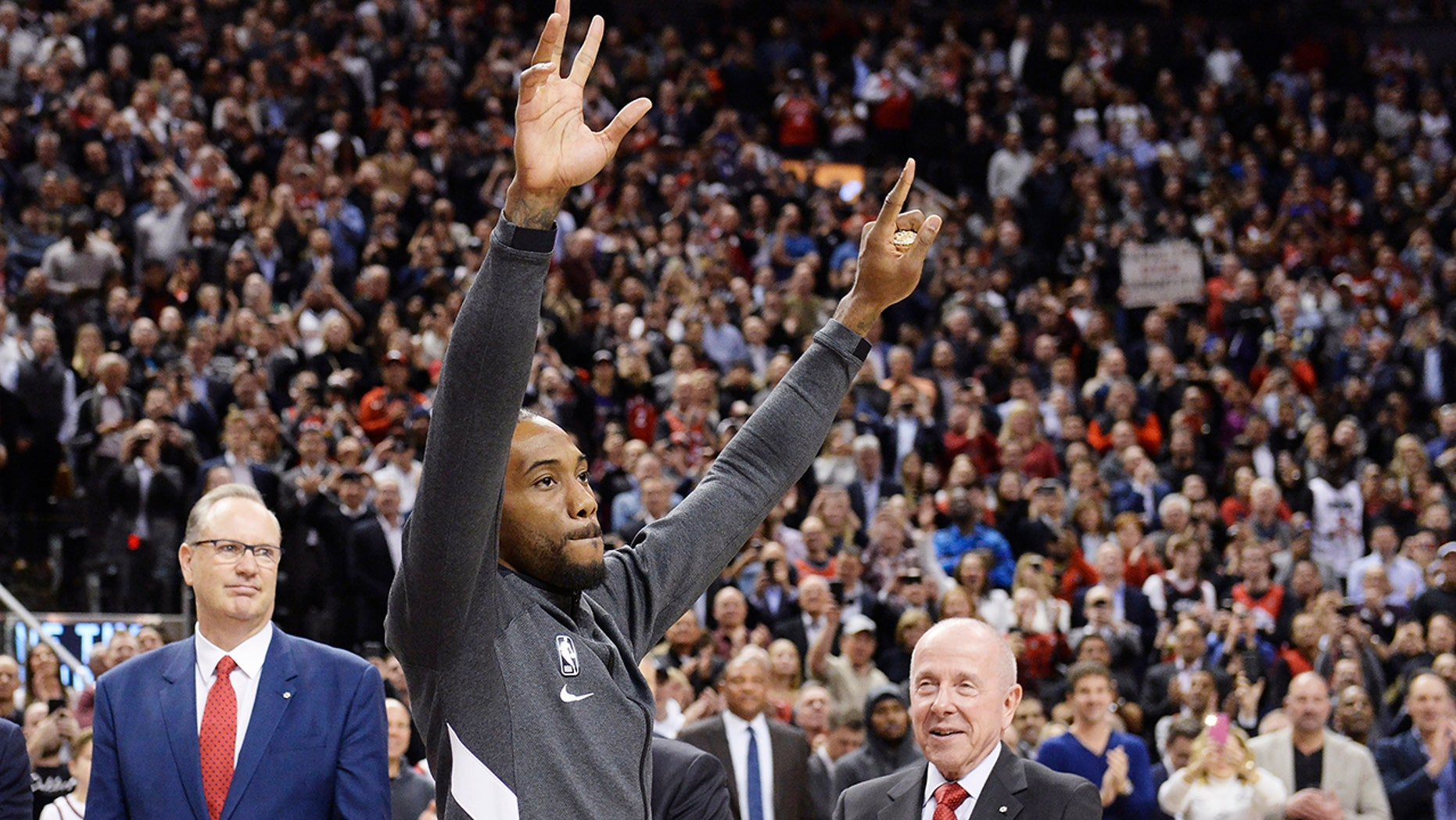 Former Toronto Raptors and now Los Angeles Clippers forward Kawhi Leonard salutes the crowd as he receives his 2019 NBA championship ring prior to an NBA basketball game, Wednesday, Dec. 11, 2019, in Toronto. (Nathan Denette/The Canadian Press via AP)