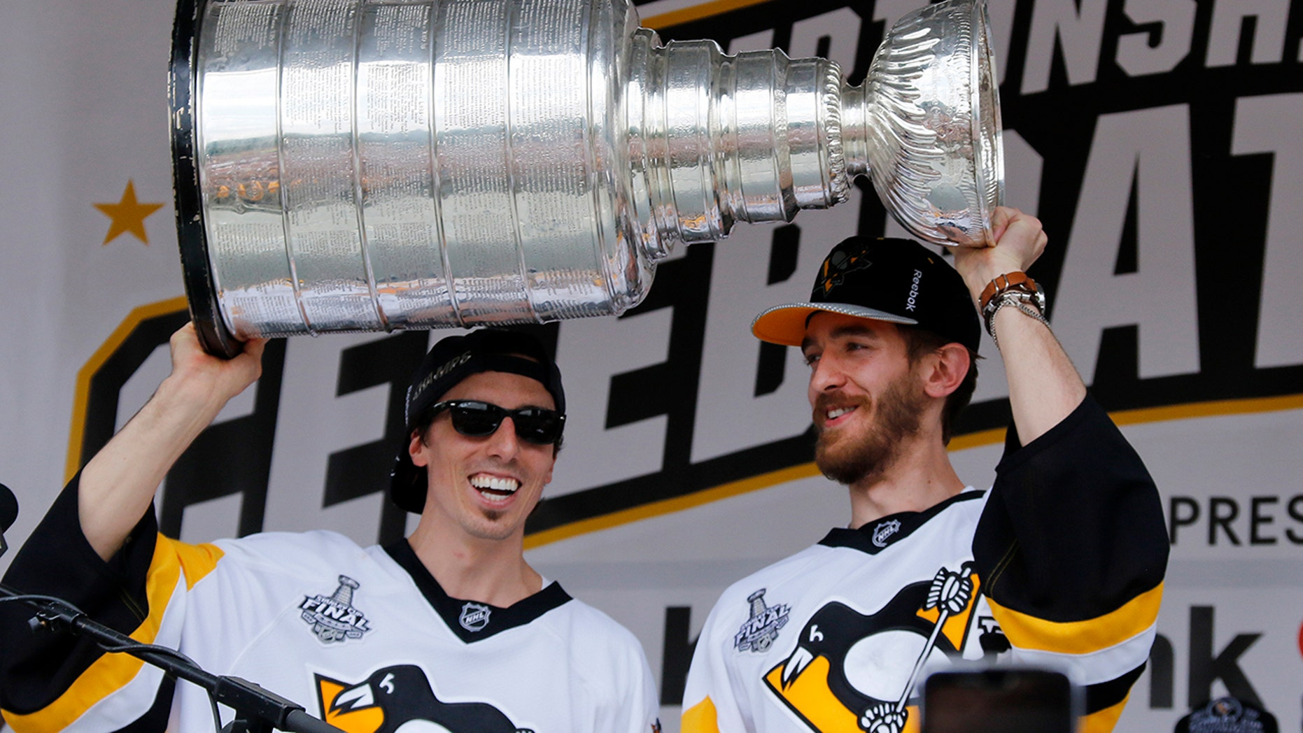 FILE - In this Wednesday, June 14, 2017, file photo, Pittsburgh Penguins goalies Marc-Andre Fleury, left, and Matt Murray hold the Stanley Cup on stage after riding in the Stanley Cup victory parade in Pittsburgh. Managing top goaltenders' schedules is the NHL's version of load management. Each of the past five Stanley Cup-winning goalies started fewer than 60 games in the regular season, along with three of the past five runners up. (AP Photo/Gene J. Puskar, File)