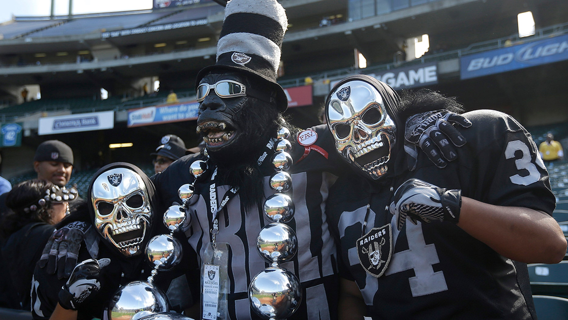 FILE - In this Sept. 29, 2013, file photo, Oakland Raiders fan Gorilla Rilla, center, poses for photographs with fans before an NFL football game between the Oakland Raiders and the Washington Redskins in Oakland, Calif. The Raiders' final scheduled game in Oakland on Sunday, Dec. 15, 2019, will be an emotional one for players and coaches, as well as fans. (AP Photo/Marcio Jose Sanchez, File)