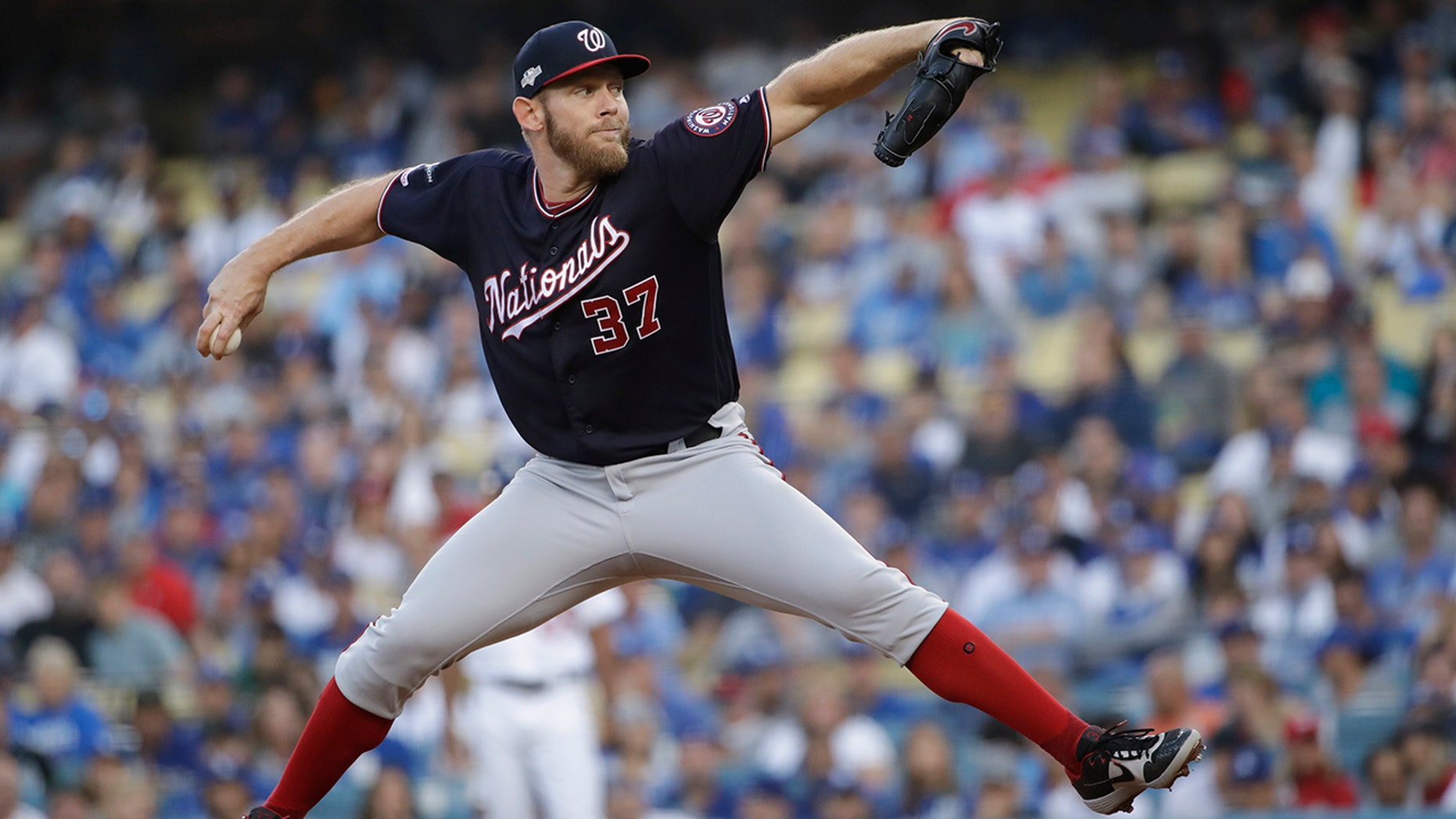 FILE - In this Oct. 9, 2019, file photo, Washington Nationals starting pitcher Stephen Strasburg throws to a Los Angeles Dodgers batter during the first inning in Game 5 of a baseball National League Division Series, in Los Angeles. World Series MVP Stephen Strasburg is staying with the Washington Nationals. The right-hander has agreed to a record $245 million, seven-year contract, a person familiar with the negotiations told The Associated Press on Monday, Dec. 9, 2019. The person spoke on condition of anonymity at baseball's annual winter meetings because the agreement had not been announced. (AP Photo/Marcio Jose Sanchez, File)
