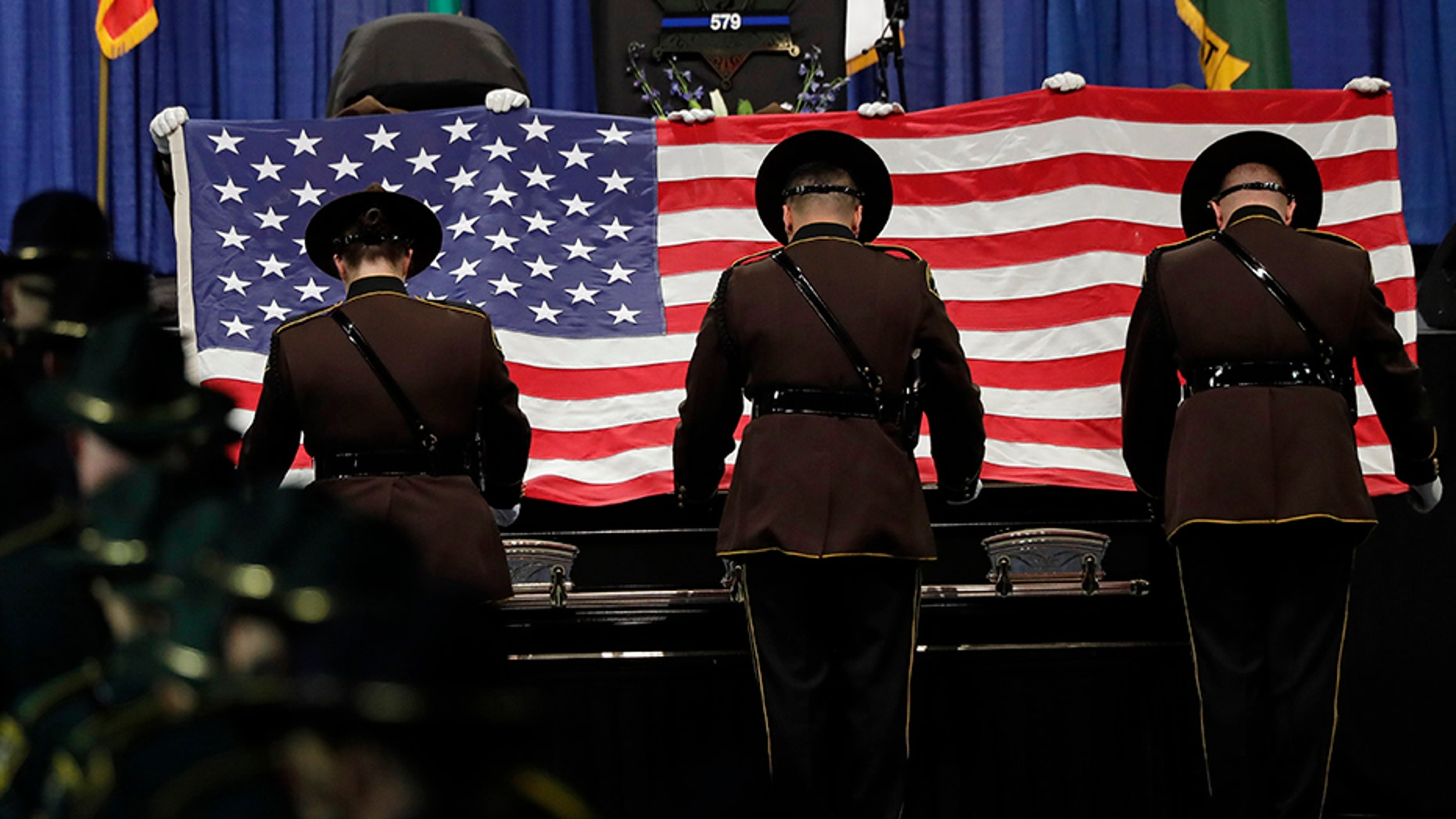 Pierce County Sheriff's deputies fold the U.S. flag that draped the casket of Pierce County Sheriff's Deputy Cooper Dyson, on Monday, Dec. 30, during a memorial service in Tacoma, Wash. (AP)