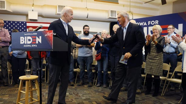 Democratic presidential candidate former Vice President Joe Biden hands the microphone to former Iowa Gov. Tom Vilsack, right, after speaking to local residents during a bus tour stop at Water's Edge Nature Center, Monday, Dec. 2, 2019, in Algona, Iowa. (AP Photo/Charlie Neibergall)
