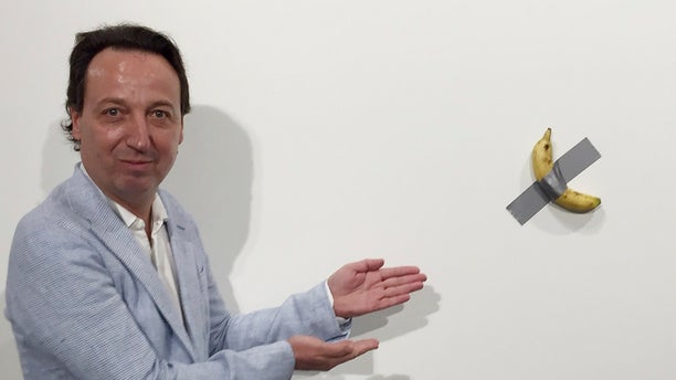 """In this photo, gallery owner Emmanuel Perrotin poses next to Italian artist Maurizio Cattlelan's """"Comedian"""" at the Art Basel exhibition in Miami Beach, Fla. The work sold for $120,000. A Miami couple who bought a headline-grabbing banana duct-taped to a wall say they acknowledge the absurdity of the artwork, but believe it will become an icon and plan to gift it to a museum. (Siobhan Morrissey via AP)"""
