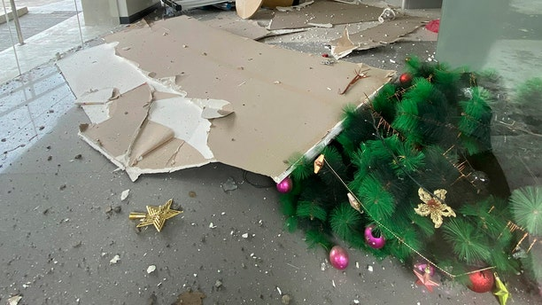 A toppledChristmas tree and other debris are seen inside a building after a strong earthquake shook Digos, Davao del Sur province, southern Philippines on Sunday Dec. 15, 2019. (Philippine Red Cross via AP)