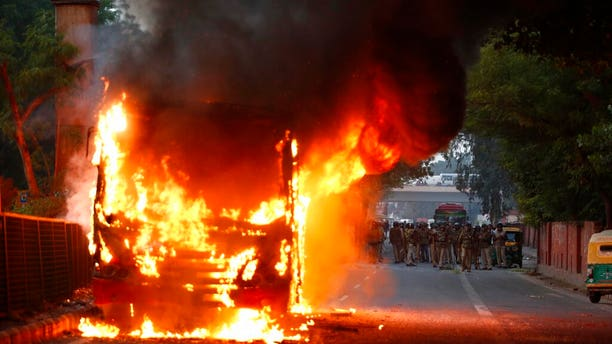 A passenger bus up in flames during a protest against Citizenship Amendment Act in New Delhi, India, on Sunday. (AP Photo)