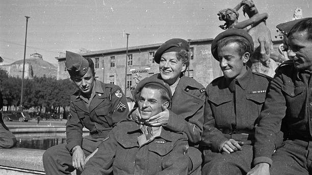 December 15, 1945: During an ENSA tour of Italy, singer and comedienne Gracie Fields (1898-1979) poses with members of the Allied Forces in Rome.