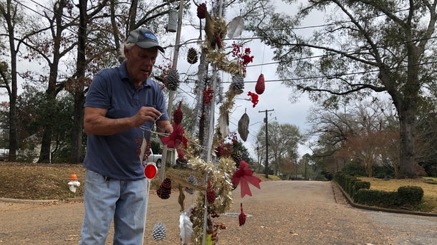 John Drummond checking on the makeshift Christmas tree he placed over a pothole on the street where he lives in McComb, Mississippi. He and neighbors said they decided to decorate the tree to get the attention of city officials. (Fox News/Charles Watson)