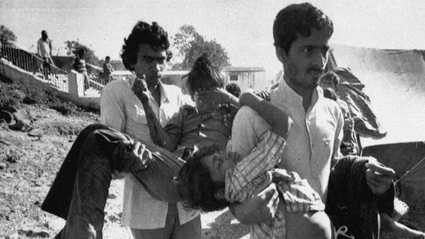 FILE – In this Dec. 5, 1984 file photo, two men carry to a hospital children blinded by the Union Carbide chemical pesticide leak in Bhopal, India.(AP Photo/Sondeep Shankar, File)