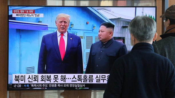 """People watch a TV screen showing a file image of North Korean leader Kim Jong Un and U.S. President Donald Trump, left, during a news program at the Seoul Railway Station in Seoul, South Korea, Tuesday, Dec. 31, 2019. The sign reads: """"North Korea and the United States can't restore confidence."""" (AP Photo/Ahn Young-joon)"""