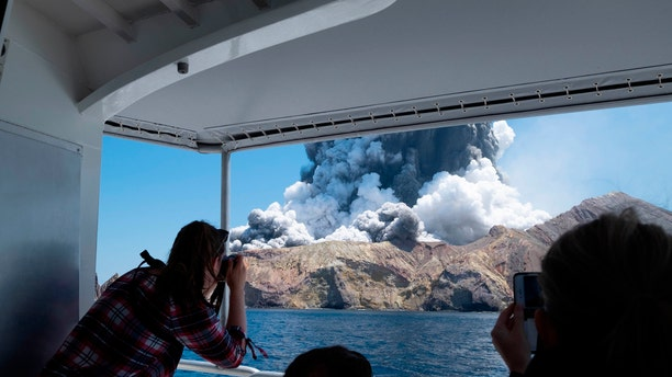 In this Monday, Dec. 9, 2019, photo provided by Michael Schade, tourists on a boat look at the eruption of the volcano on White Island, New Zealand.