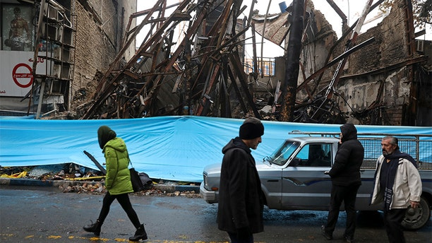 People walk past buildings that were burned during recent protests, in Shahriar, Iran, on Nov. 20.