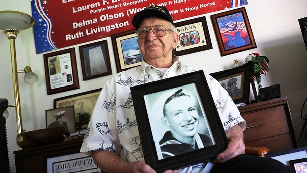 Lauren Bruner, a survivor of the USS Arizona which was attacked on Dec. 7, 1941, holds with a 1940 photo of himself at his home in La Mirada, Calif., Nov. 17, 2016. He died earlier in 2019 at age 98. (Associated Press)