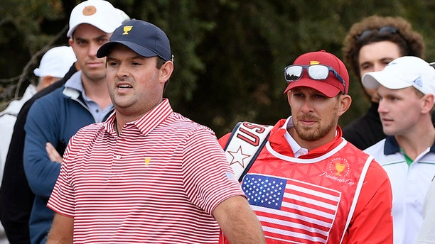 In this Dec. 12, 2019, photo U.S. team player Patrick Reed and his caddie, Kessler Karain, right, look for a potential shot during the President's Cup golf tournament at Royal Melbourne Golf Club in Melbourne. (AP Photo/Andy Brownbill)