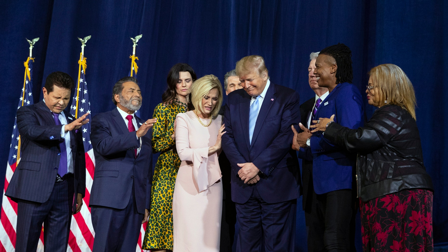 """Faith leaders pray over President Donald Trump during an """"Evangelicals for Trump Coalition Launch"""" at King Jesus International Ministry, Friday, Jan. 3, 2020, in Miami. (AP Photo/ Evan Vucci)"""
