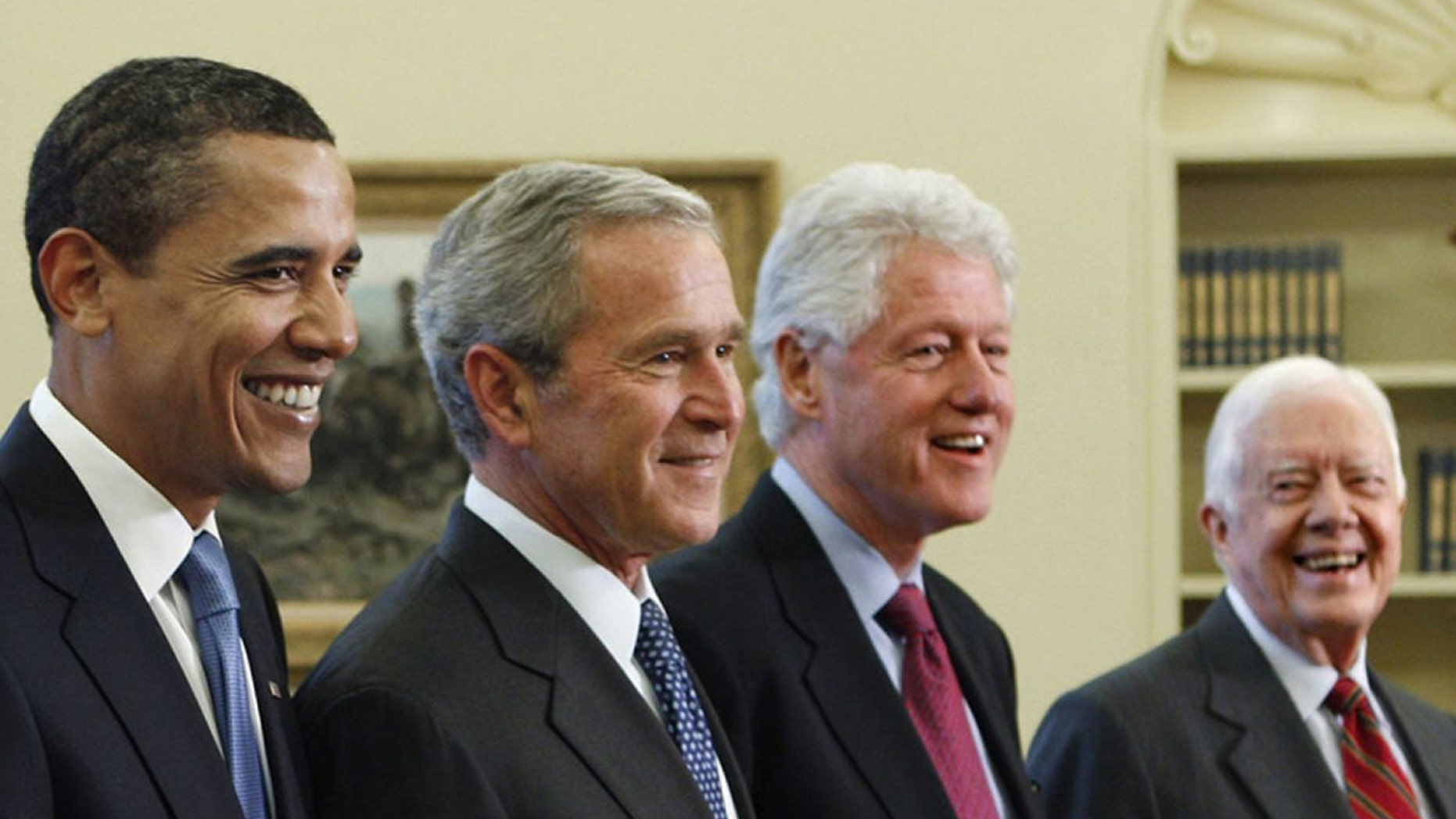 Former Presidents Barack Obama, George W. Bush, Bill Clinton, and Jimmy Carter, pose in the Oval Office of the White House.