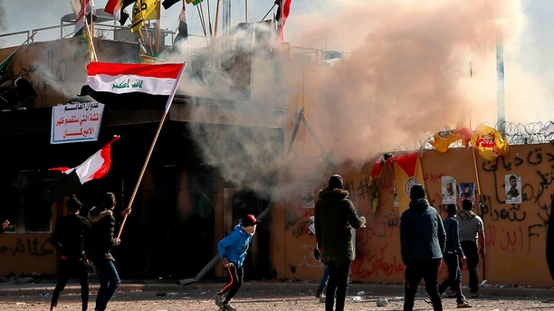 U.S. troops fired tear gas on Wednesday to disperse pro-Iran protesters who were gathered outside the U.S. Embassy compound in Baghdad for a second day as dozens of pro-Iranian militiamen and their supporters had camped out at the gates of the embassy in Baghdad, where they stayed the night. (AP Photo/Khalid Mohammed)
