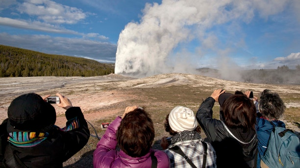In this 2011, file photo, tourists photograph Old Faithful erupting on schedule late in the afternoon in Yellowstone National Park, Wyo. Two men who pleaded guilty to trespassing on the cone of Old Faithful Geyser in Yellowstone National Park were sentenced to 10 days in jail and have been banned from the park for five years. (AP Photo/Julie Jacobson, File)