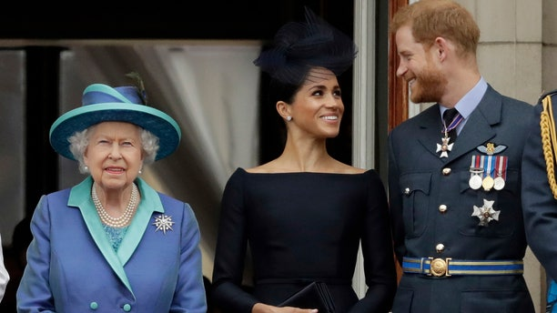 """In this Tuesday, July 10, 2018 file photo Britain's Queen Elizabeth II, and Meghan the Duchess of Sussex and Prince Harry watch a flypast of Royal Air Force aircraft pass over Buckingham Palace in London. As part of a surprise announcement distancing themselves from the British royal family, Prince Harry and his wife Meghan declared they will """"work to become financially independent"""" — a move that has not been clearly spelled out and could be fraught with obstacles."""
