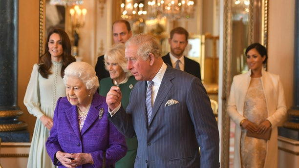 In this March 5, 2019 file photo, Britain's Queen Elizabeth II is joined by Prince Charles, the Prince of Wales, and at rear, from left, Kate, Duchess of Cambridge, Camilla, Duchess of Cornwall, Prince William, Prince Harry and Meghan, Duchess of Sussex during a reception at Buckingham Palace, London to mark the 50th anniversary of the investiture of the Prince of Wales.