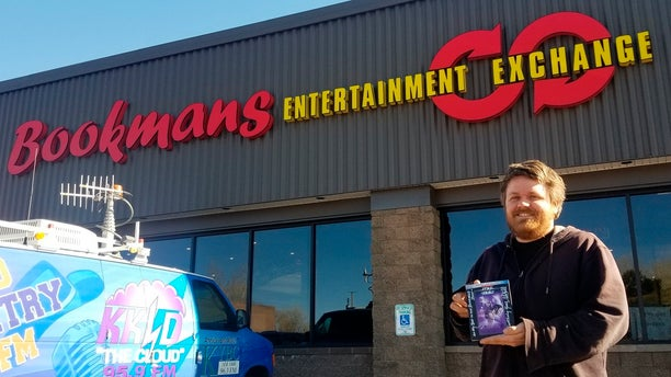 Bookmans Entertainment Exchange general manager Micheil Salmons stands in front of the store in Flagstaff, Ariz., holding a DVD autographed by Star Wars actor Mark Hamill. (Scott Buffon/Arizona Daily Sun via AP)