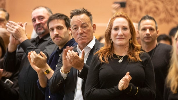 Bruce Springsteen, center, and Patti Scialfa, right, applaud as their son Sam Springsteen is sworn in as a Jersey City, N.J., firefighter. (Jennifer Brown/Jersey City Mayor's Office via AP)