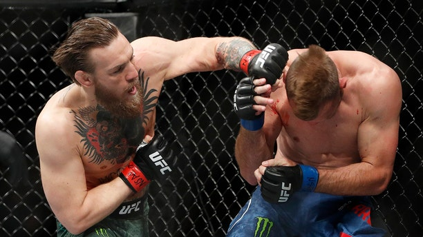 """Conor McGregor hits Donald """"Cowboy"""" Cerrone during a UFC 246 welterweight mixed martial arts bout Saturday, Jan. 18, 2020, in Las Vegas. (Associated Press)"""