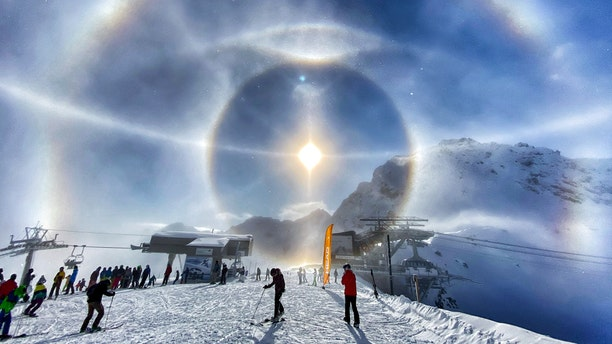 This breathtaking photo shows the moment that ice crystals froze in midair, causing a halo effect around the beaming Sun. (Credit: SWNS)