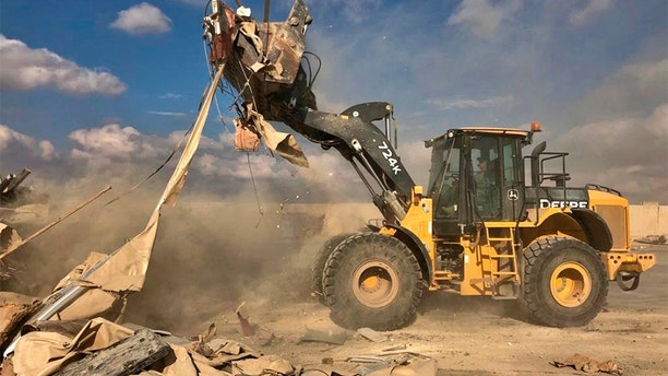 A bulldozer clears rubble and debris at the base. (AP)