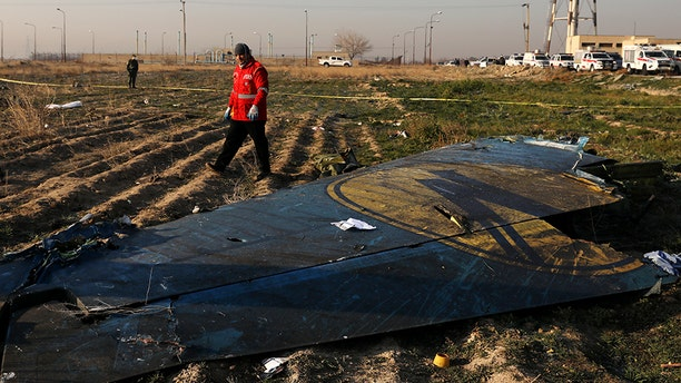 A rescue worker searches the scene where a Ukrainian plane crashed.