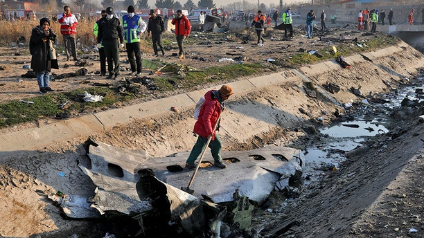 Rescue workers inspect the scene where a Ukrainian plane crashed in Shahedshahr, southwest of the capital Tehran, Iran, on Wednesday.
