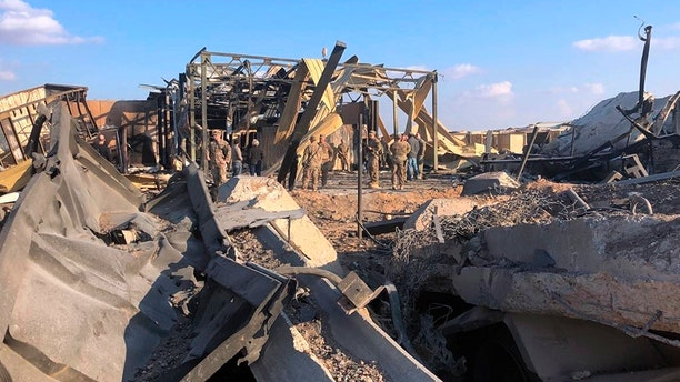 U.S. soldiers and journalists inspect the rubble at a site of Iranian bombing, in Al Assad Air Base, in Anbar, Iraq.