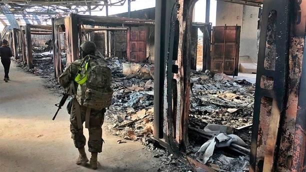 U.S. soldiers walk past damage at the Ain al-Asad base on Monday. (AP)