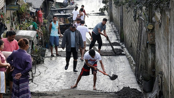 Residents clean ash outside their homes as Taal Volcano still spews ash on Monday Jan. 13, 2020, in Tagaytay, Cavite province, south of Manila, Philippines. (AP Photo/Aaron Favila)