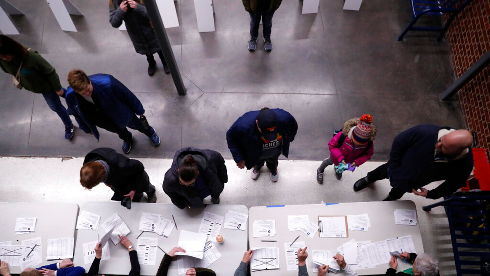 Caucus goers check in at a caucus at Roosevelt High School, Monday, Feb. 3, 2020, in Des Moines, Iowa. (AP Photo/Andrew Harnik)