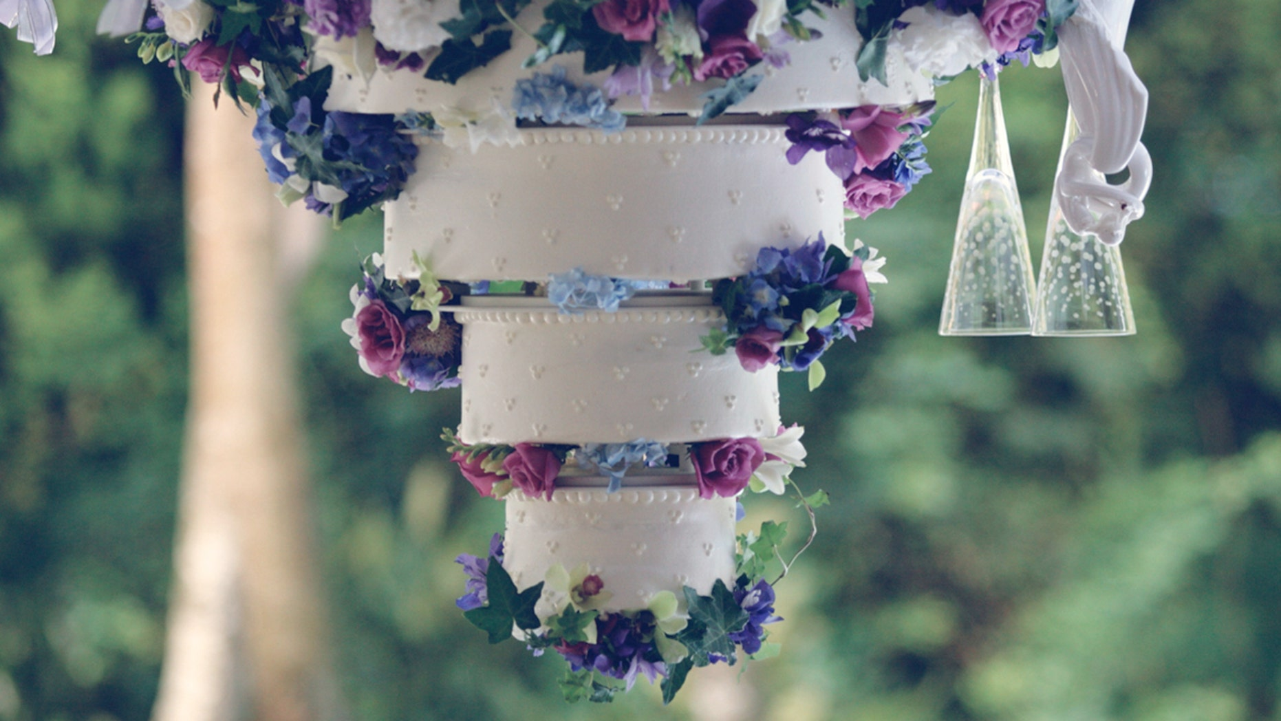 An elegant catered white wedding cake with 3 tiers and latticed frosting.