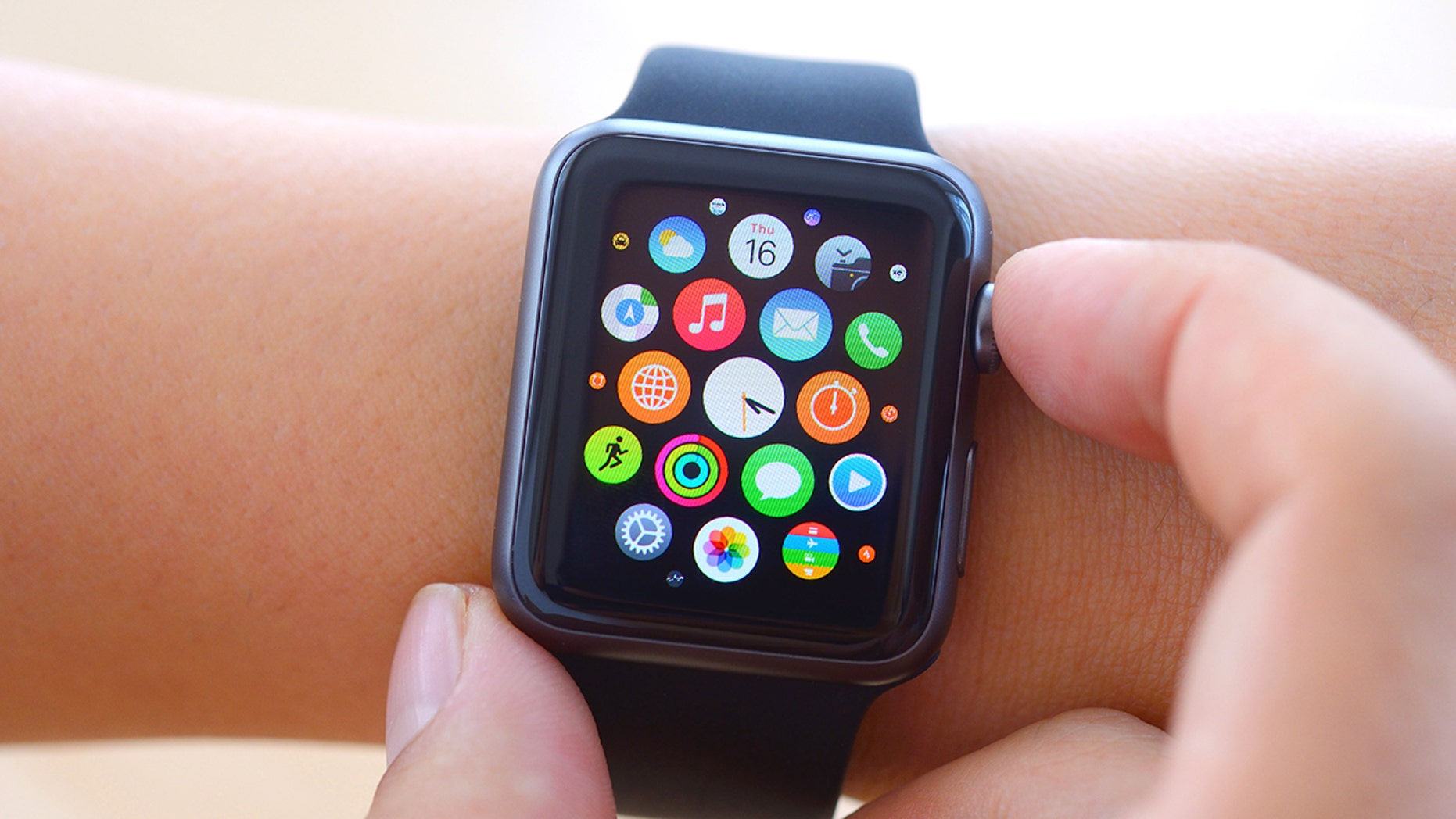 digital products İstanbul, Turkey - July 16 2015: Hand touching an Apple Watch displaying home screen. Apple Watch is a smart watch, devices developed by Apple Inc.