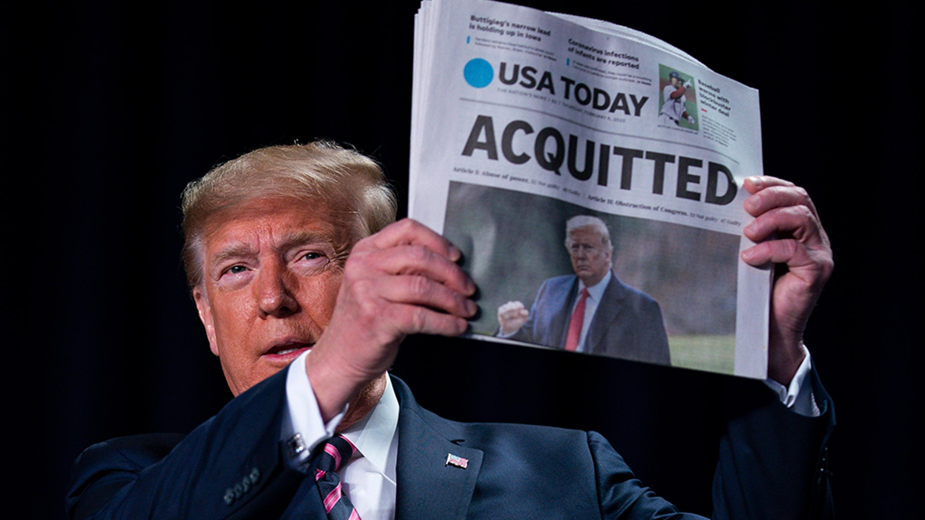 President Donald Trump holds up a newspaper with the headline that reads