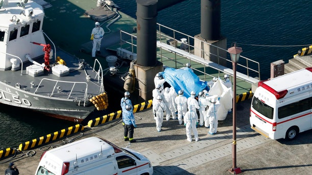 Medical workers in protective suits lead a passenger tested positive for a new coronavirus from the cruise ship Diamond Princess at Yokohama Port in Yokohama, south of Tokyo, Wednesday, Feb. 5, 2020.. (Hiroko Harima/Kyodo News via AP)