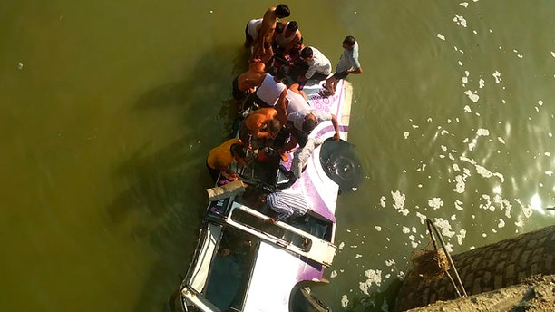 Rescuers look for survivors after a bus plunged into the Maze River in Lakheri area near Kota in Rajasthan state, India, Wednesday, Feb. 26, 2020. At least 24 people from a wedding party were killed in the accident. (AP Photo/Sahil Sheri)