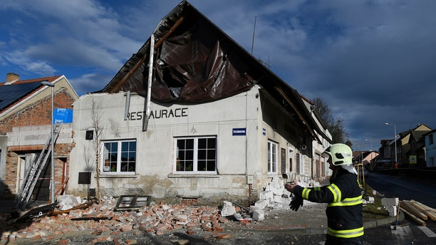 A fireman passes by a house which roof was moved due to a strong storm in Kladno, Czech Republic, Monday, Feb. 10, 2020.