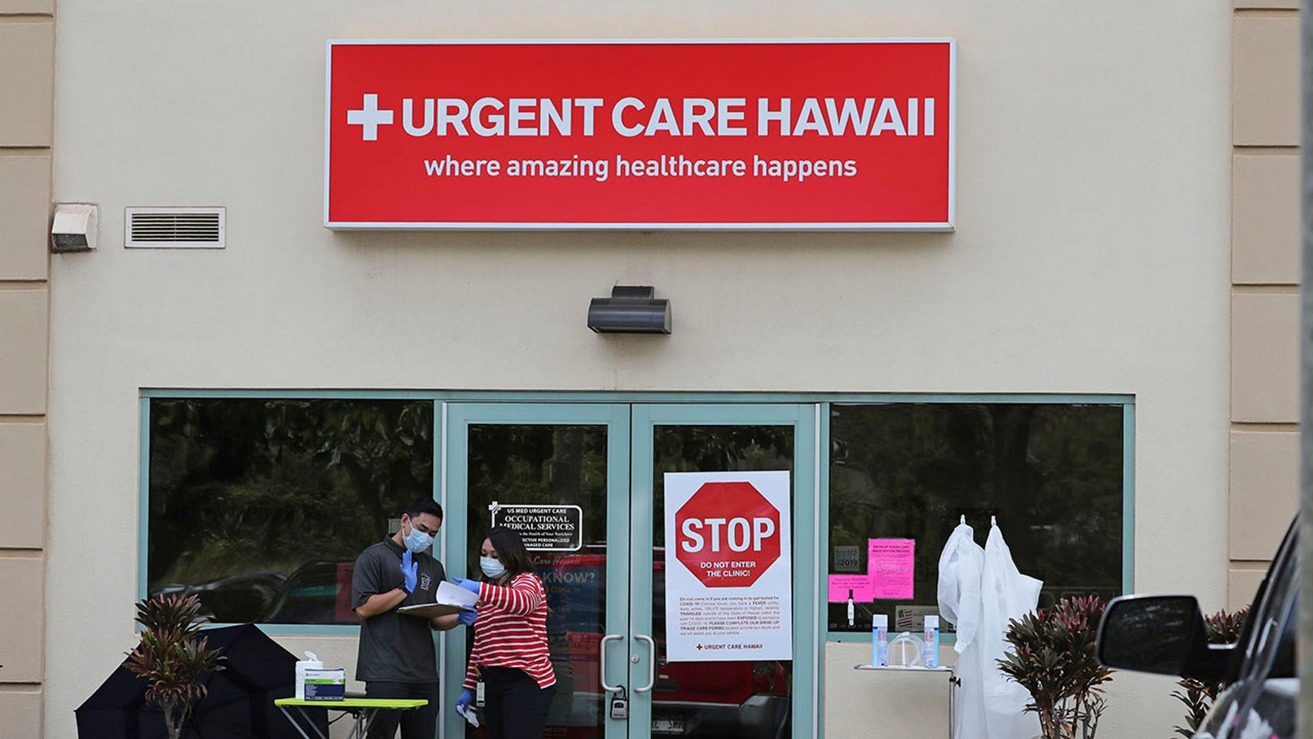 People wearing medical gear stand outside an Urgent Care Hawaii medical clinic March 13, 2019, in Pearl City, Hawaii. AP Photo/Marco Garcia)