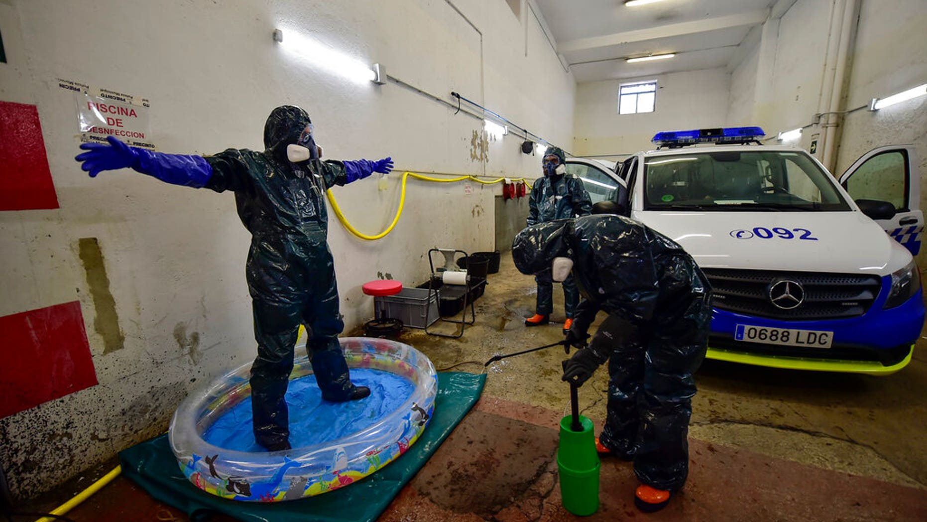 Volunteer workers of Search and Rescue (SAR) with special equipment, disinfect a volunteer while disinfecting police car at Local Police station to prevent the spread of coronavirus COVID-19, in Pamplona, northern Spain, Sunday, March 22, 2020. (AP Photo/Alvaro Barrientos)