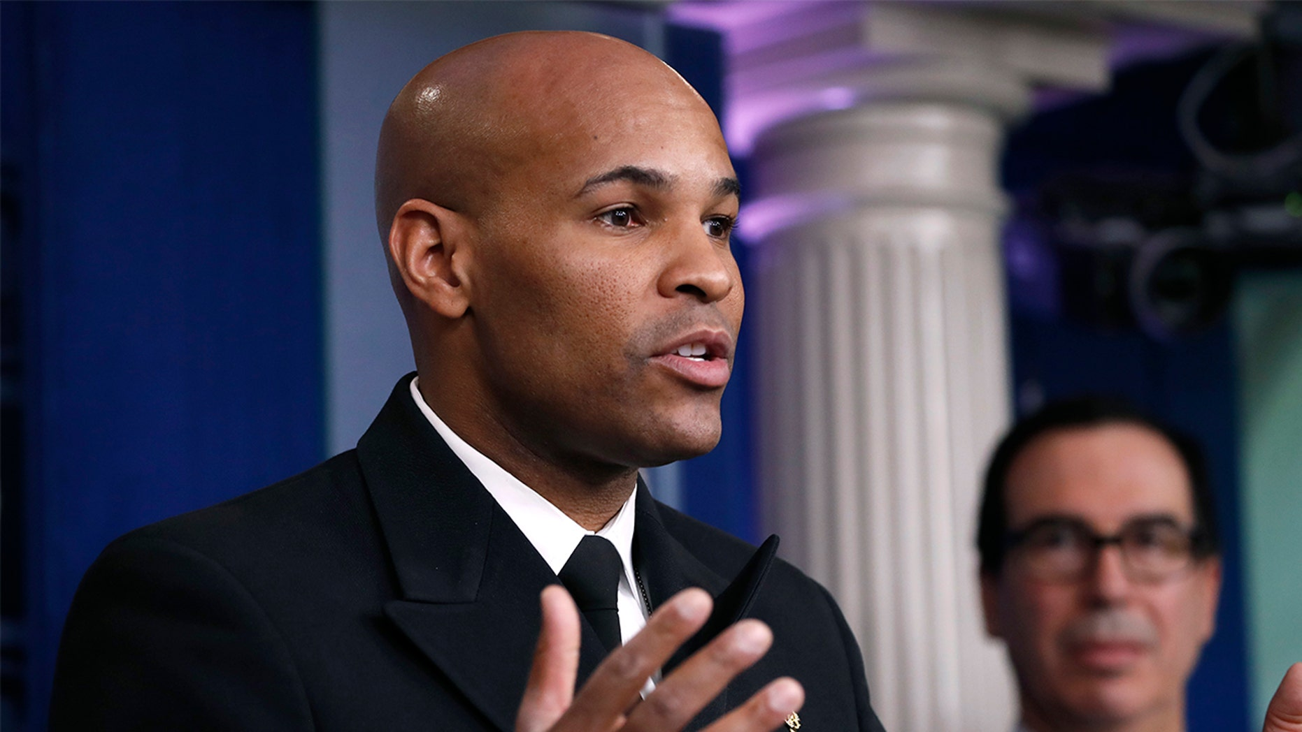 U.S. Surgeon General Jerome Adams speaks during a briefing on coronavirus in the Brady press briefing room at the White House, Saturday, March 14, 2020, in Washington, as Treasury Secretary Steven Mnuchin listens. (AP Photo/Alex Brandon)