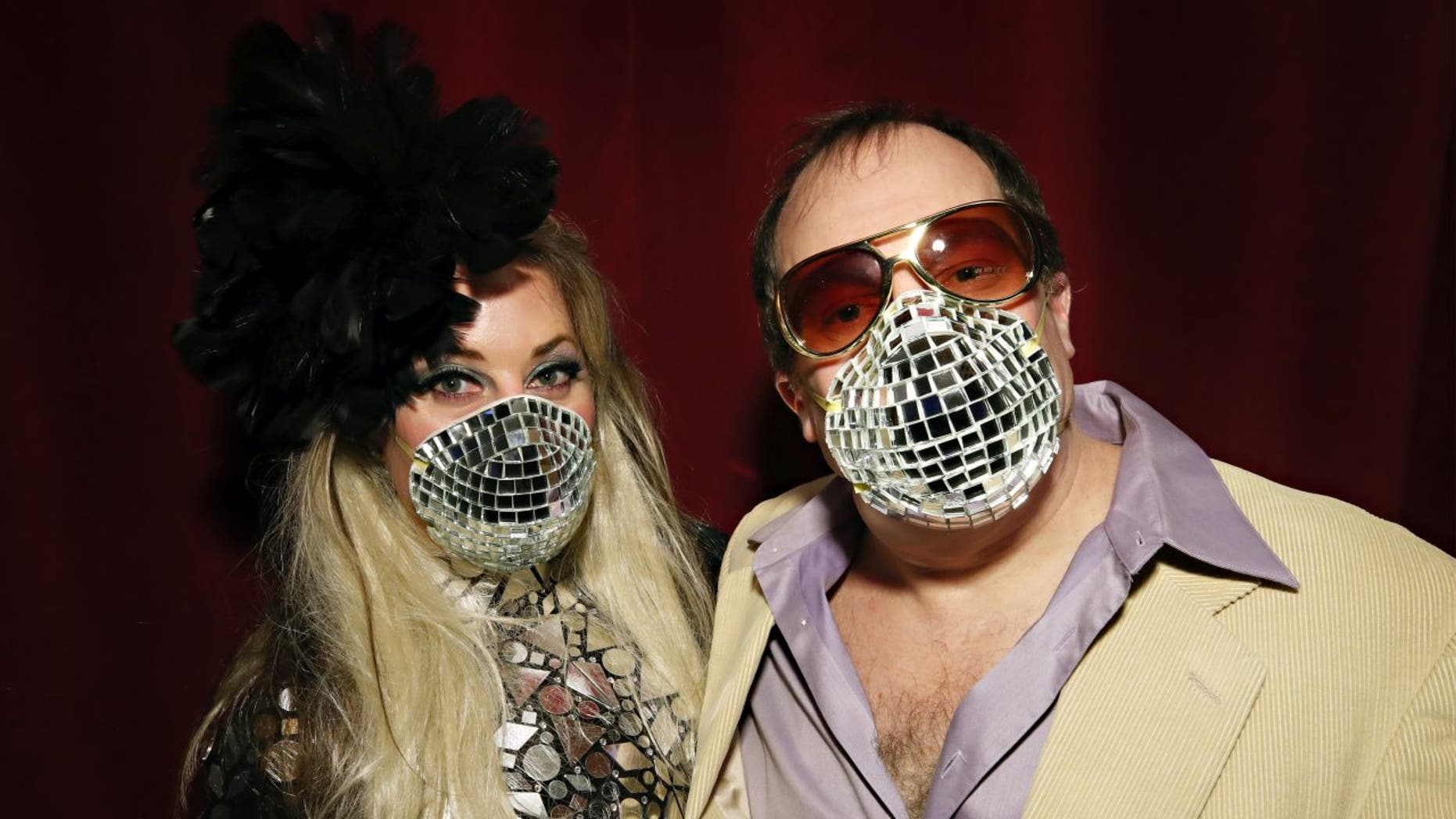"""Allison Eden and Gary Goldenstein wear decorated masks inspired by the Coronavirus disease (COVID-19) threats during """"Studio 54: Night Magic"""" Opening Night at the Brooklyn Museum on March 11, 2020."""