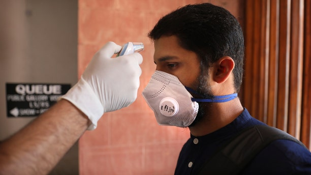 A security official checks the temperature of a visitor as a precaution against the new coronavirus at the Parliament House in New Delhi, India, Tuesday, March 17, 2020.