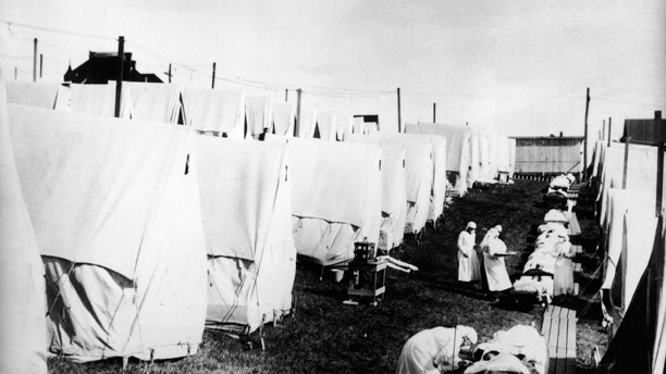 Masked doctors and nurses treat flu patients lying on cots and in outdoor tents at a hospital camp during the influenza epidemic of 1918. (Photo by Hulton Archive/Getty Images)