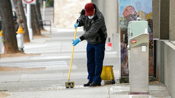 A man cleans a sidewalk in downtown Sacramento, Calif., Monday, March 23, 2020. (AP)